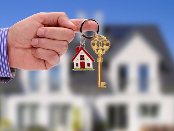 An image of keys in front of a house.